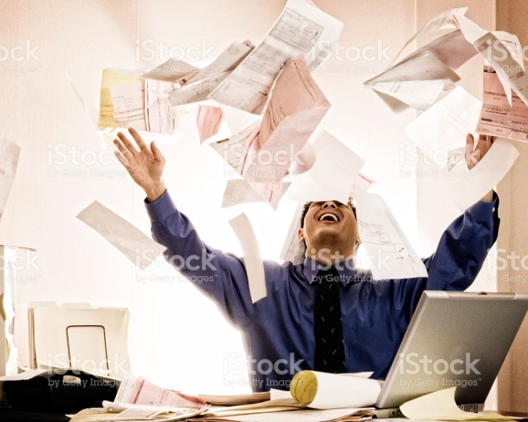 Happy businessman tossing documents into air at desk.